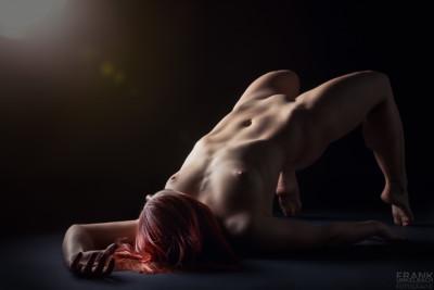Rothaarige junge Frau liegt nackt auf dem Boden und macht auf Zehenspitzen eine Brücke. Ein Streiflicht modelliert ihren athletischen Körper.