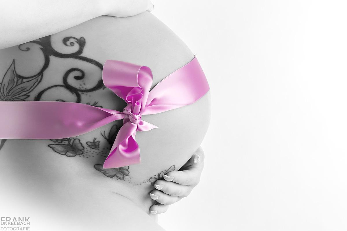 Hände mit lackierten Fingernägeln umfassen tätowierten Babybauch mit einer rosa Schleife