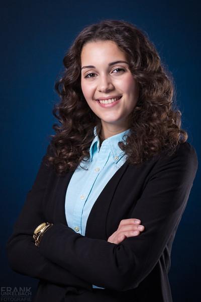 Bewerbungsfoto einer jungen brünetten Frau mit fantastischen Locken. Sie trägt eine hellblaue Bluse und ein schwarzes Jacket.