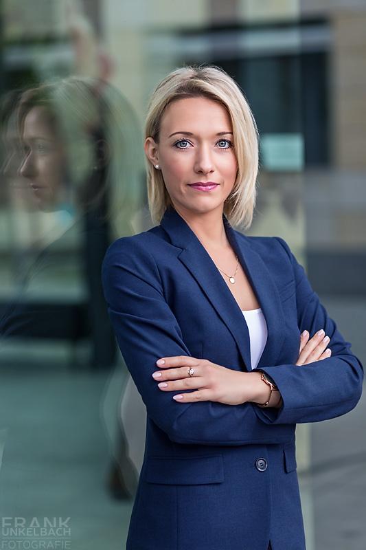 Business-Portrait einer attraktiven blonden Frau mit blauem Jacket und weißem Top. Schöne Spiegelung in einer Glasfasade.
