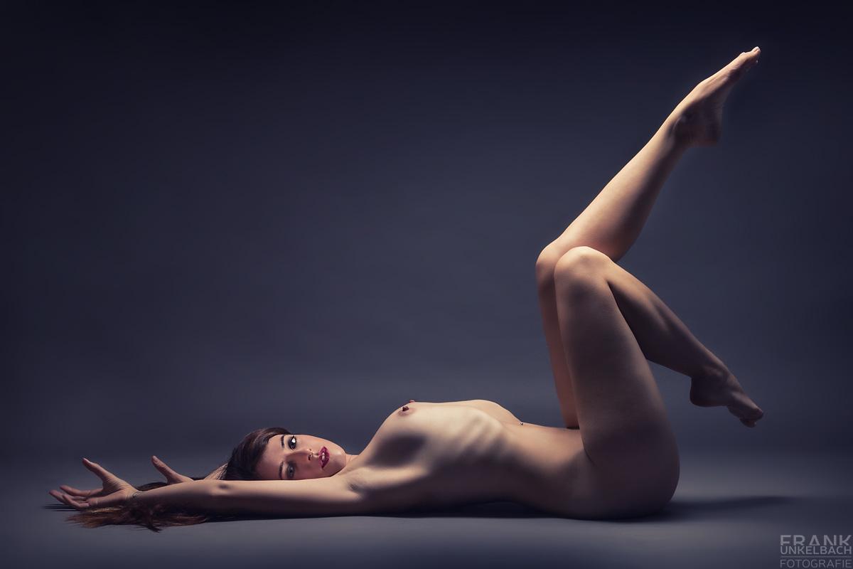 Junge sexy Frau mit langen Haaren liegt nackt auf dem Rücken und streckt Ihre tollen Beine in spannender Pose nach oben.