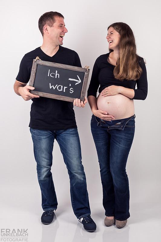 Lustige Aufnahme eines Paares. Die schwangere Frau zeigt Ihren Babybauch und der Mann zeigt, dass er der Vater ist.