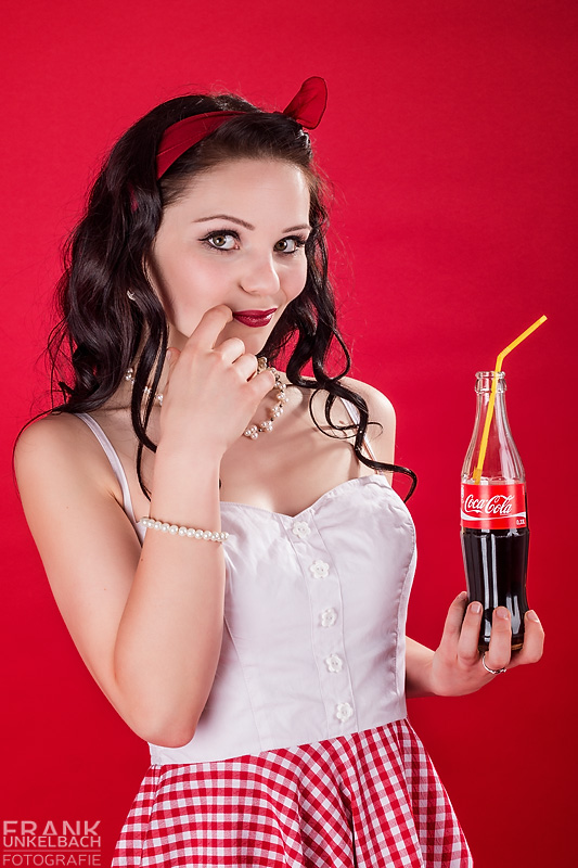 Portrait einer dunkelhaarigen Frau im Rockabilly-Stil mit einer Schleife im Haar und einer Flasche Coca-Cola in der Hand