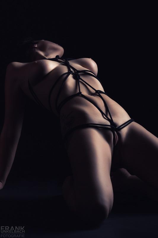 Junge provozierende Frau kniet nackt auf dem Boden. Sie trägt ein Bondage - ein aus schwarzen Seilen geknüpfter Harness.