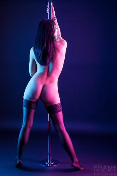 Sexy Pole-Tänzerin mit langen schwarzen Haaren steht in halterlosen Strümpfen an einer Pole Dance Stange. Ihr knackiger Po und ihre langen Beine werden in farbiges Licht getaucht.