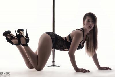 Sexy Blondine in schwarzem Spitzenbody und goldenen High Heels kniet auf allen Vieren vor einer Pole Dance Stange.
