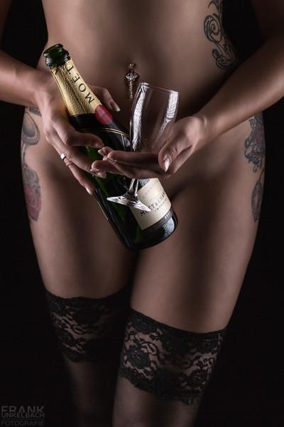 Junge Frau mit sexy Beinen in halterlosen Strümpfen und Piercing hält nackt eine Flasche Champagner und ein Sektglas in der Hand.