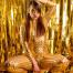Frau in einem sexy goldenen Anzug und goldener Maske sitzt mit schwarzen High Heels in provokanter Pose vor einem goldenen Hintergrund.