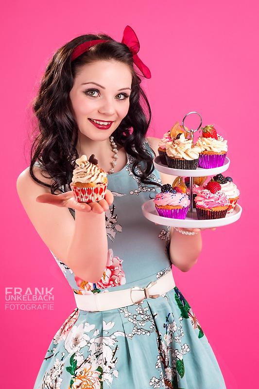 Attraktive Frau im Rockabilly-Stil und einer roten Schleife im Haar trägt ein blaues geblümtes Kleid. In ihren Händen hält sie ein Tablett leckeren Cupcakes.