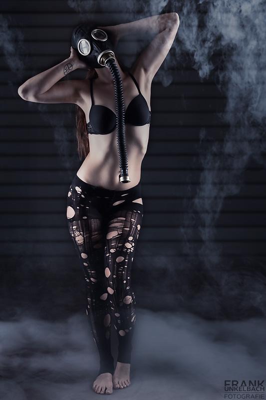 Schlanke langhaarige Frau in zerrissener Strumpfhose, schwarzem BH und Gasmaske mit Schlauch steht im Rauch.