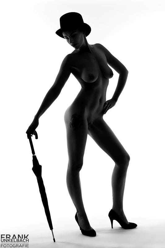 Silhouette einer schlanken großen Frau mit langen Beinen. Bis auf einen Zylinder und High Heels ist sie nackt. In der Hand hält sie einen Schirm.