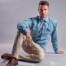 Attraktiver junger Mann sitzt in Business-Kleidung auf dem Boden. Er trägt ein blaues Hemd, eine beige Hose und braune Schuhe.