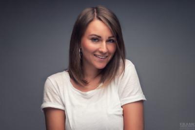 Junge hübsche Frau mit sexy Augen, bezauberndem Lächeln und langen Haaren schaut in weißem Top spitzbübisch in die Kamera.