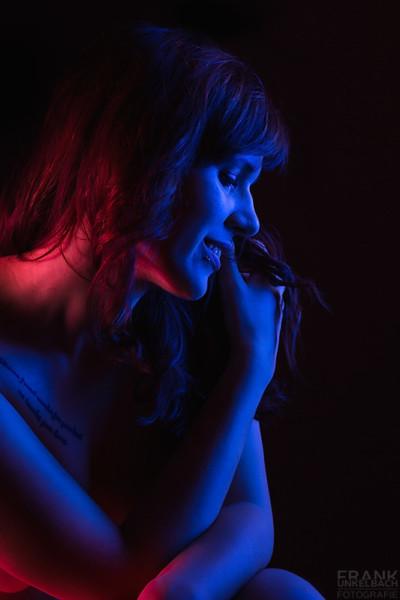 Sinnliches Portrait einer brünetten Frau, die mit den Armen vor der Brust auf einem Stuhl sitzt und mit blauem und pinkem Licht angeleuchtet wird.