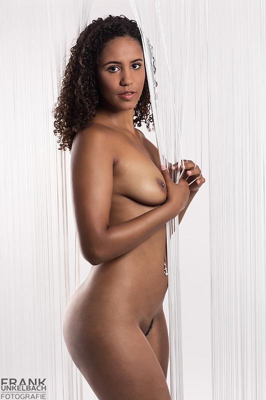 Hübsche dunkelhäutige Frau steht in sexy Pose in einem Vorhang und spielt mit Ihren Fingern an den Fäden.