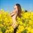 Langhaarige Frau steht nackt in einem Rapsfeld. Der gelb blühende Raps bildet einen schönen Kontrast zum blauen Himmel.