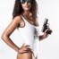 Sexy Frau mit verspiegelter Sonnenbrille und einer Walther P99 Pistole. Sie trägt einen Badeanzug mit der Aufschrift BAD BITCH.
