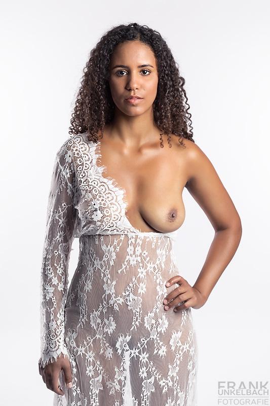 Eine dunkelhaarige Frau schaut selbstbewusst frontal in die Kamera. Sie trägt ein durchsichtiges Netzkleid, das nur eine Brust bedeckt.