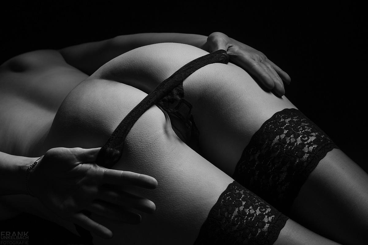 Bodypart-Aufnahme einer jungen Frau in schwarzen halterlosen Strümpfen. Sie streift ihren Tanga über ihren sexy Po.
