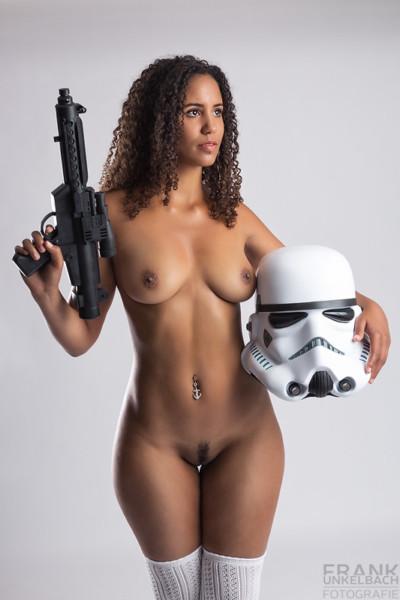 Junges dunkelhäutiges nacktes Mädchen mit schwarzen Haaren, weißen Overknees, Maschinengewehr und Sturmtrupplerhelm (Star Wars).
