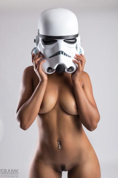 Anonymer Akt eines jungen dunkelhäutigen Mädchens, Sie posiert nackt mit Sturmtrupplerhelm auf dem Kopf (Star Wars).