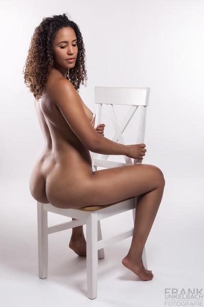 Dunkelhäutiges Mädchen mit krausen Locken sitzt nackt auf einem weißen Stuhl. Ihr Po und Ihre Brüste zeigen Ihre sexy Kurven.
