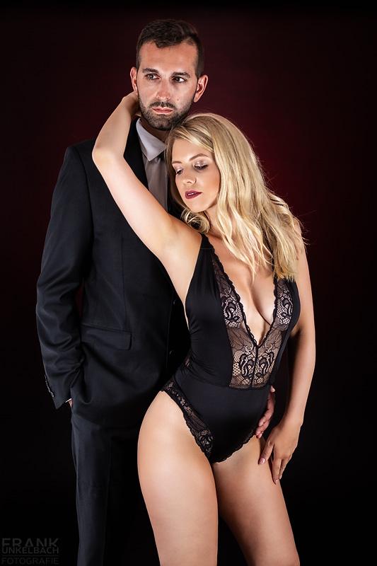 Süße langhaarige Blondine in schwarzem Spitzenbody (Dessous) schmiegt sich sexy an ihren in Anzug und Krawatte gekleideten Mann.