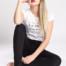 Junge stolze Blondine mit roten Lippen und langen Haaren sitzt barfuß in weißem Top und schwarzer Jeans auf dem Boden.