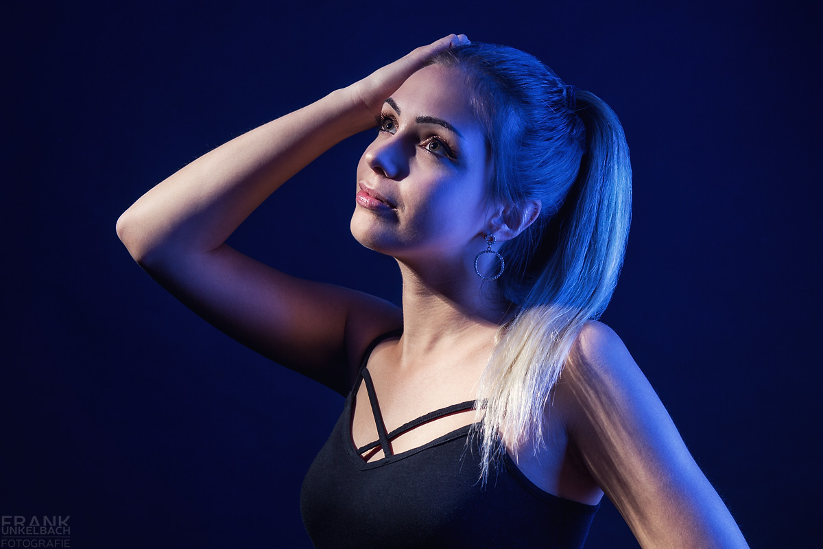 Portrait einer hübschen Blondine mit Pferdeschwanz. Ihr Haar wird blau angeleuchtet. Sie trägt Ohrringe und ein schwarzes Top.
