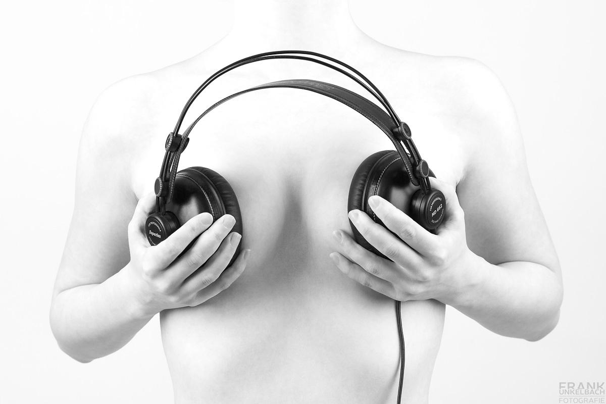 High-key-Aufnahme einer nackten Frau. Das Bodyparts-Foto zeigt die Brüste der Frau, die mich eine Kopfhörer verdeckt werden.