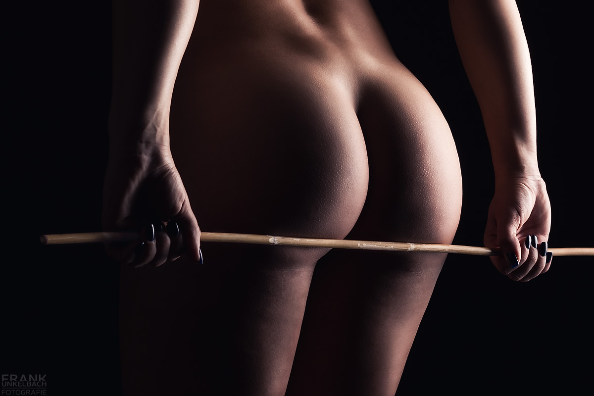 Frau mit sexy Apfelpo hält in beiden Händen einen Rorstock aus Bambus auf ihrem nackten Hintern.