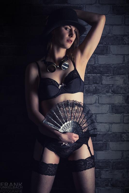 Sexy Frau in halterlosen Netzstrümpfen und Steampunk-Dessous. Auf dem Kopf trägt Sie einen Zylinder in der Hand einen Fächer.