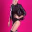 Schlankes blondes Mädchen mit sexy Beinen und schwarzen Overknees. Sie steht in einer schwarzen Lederjacke und pinkem visor cap vor einem pinkfarbenen Hintergrund.