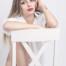 Hübsche Blondine sitzt mit angezogenem Bein rittlings auf einem weißen Stuhl. Neben Ihrem roten Lippenstift trägt sie lediglich ein weißes Hemd.