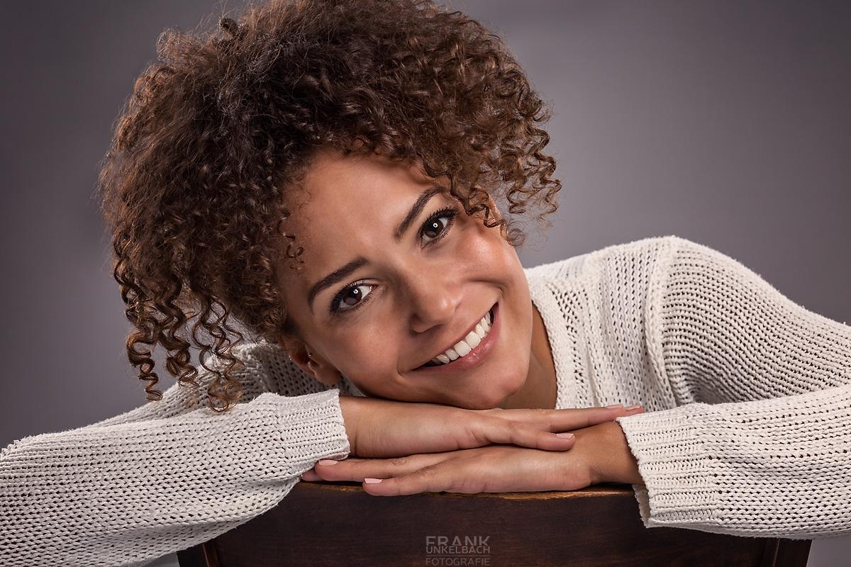 Junge attraktive dunkelhäutige Frau mit süßem Lockenkopf sitzt auf einem Stuhl. Ihr bezauberndes Lächeln vereinnahmt den Betrachter.