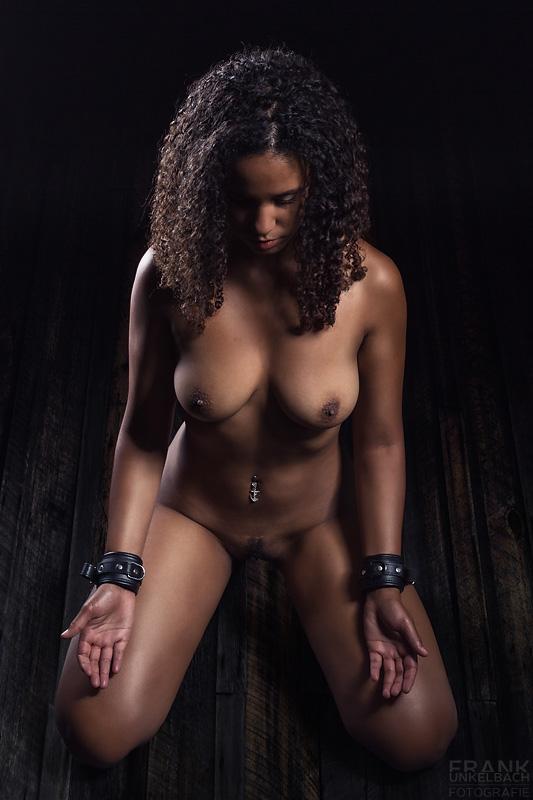 Devote Frau kniet nackt vor ihrem Meister und wartet auf Anweisungen. Um die Handgelenke trägt sie Lederriemen zur Fesselung.