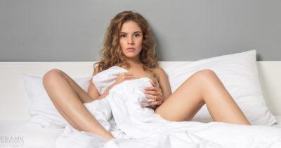 Junge Russin mit langen, lockigen, blonden Haaren sitzt mit gespreizten Beinen im Bett und verhüllt sich mit der Bettdecke.