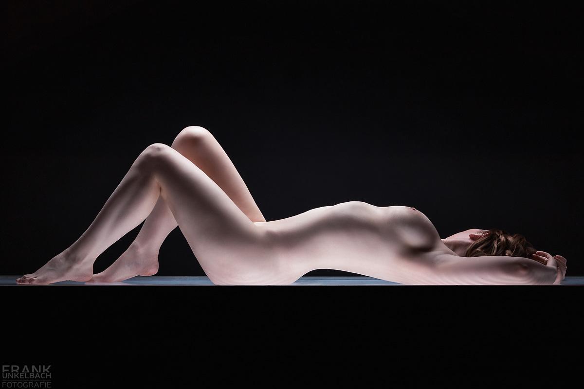 Junges rothaariges Model liegt nackt auf einem Leuchttisch. Ihre angewinkelten Beine und der durchgedrückte Rücken betonen Ihre sexy Kurven und Brüste.