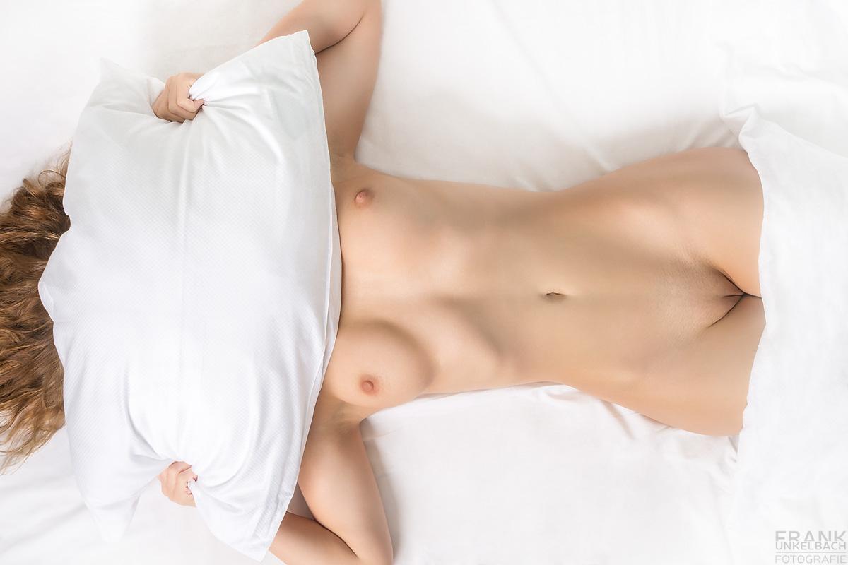 Unbekannte junge Frau liegt nackt im Bett auf dem Rücken. Man sieht ihre Brüste und ihren Intimbereich. Das Gesicht verdeckt sie mit einem Kissen.