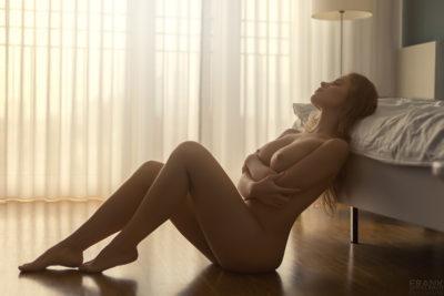 Attraktive nackte Frau sitzt vor dem Bett auf dem Boden. Sie verschränkt Ihre Arme unter Ihren Brüsten. Die warme Sonne scheint durch das Fenster.