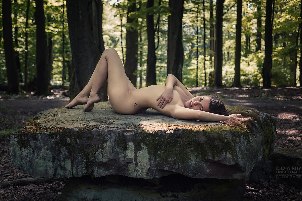 Junge Frau mit intensivem Blick und sexy Kurven liegt nackt im Wald auf einem Opferaltar. Mit einer Hand verdeckt sie ihre Brüste.