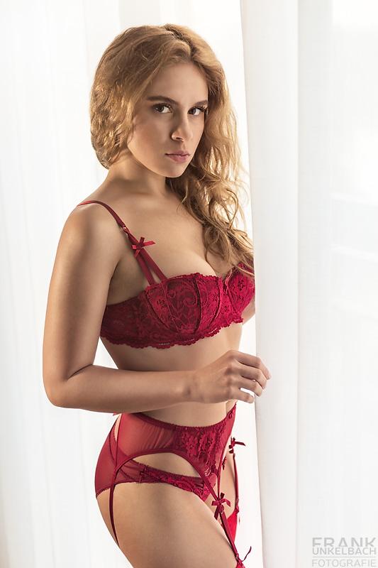 Sexy Russin in roten Dessous und Strapsen steht mit Ihren langen lockigen Haaren am Fenster. Diffuses Licht fällt durch den Vorhang und modelliert ihre perfekten Kurven.