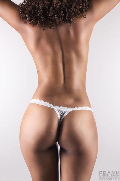 Bodypart-Aufname einer dunkelhäutige Frau mit lockigen Haaren. Sie trägt einen weißen Spitzentange, der ihren sexy Po perfekt zur Geltung bringt.