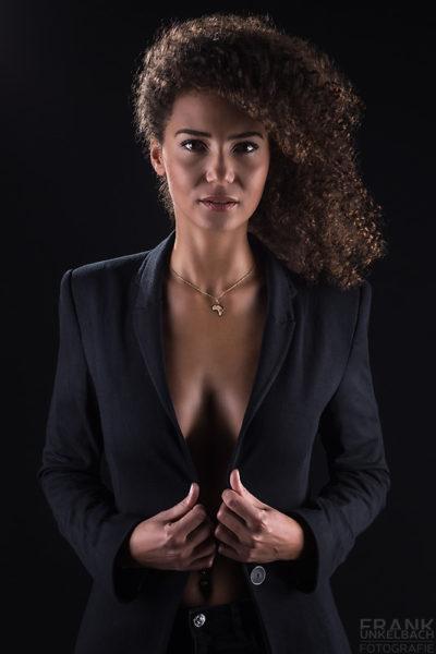 Attraktive und selbstbewusste Frau trägt ein schwarzes Jacket ohne etwas darunter. Eine goldene Kette und ein Piercing rundet ihr Outfit ab.