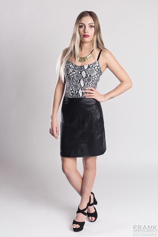 Junge schlanke Blondine mit langem Haar trägt High Heels, einen Lederrock und Schlangenleder-Top. Eine moderne Halskette rundet ihr Outfit ab.