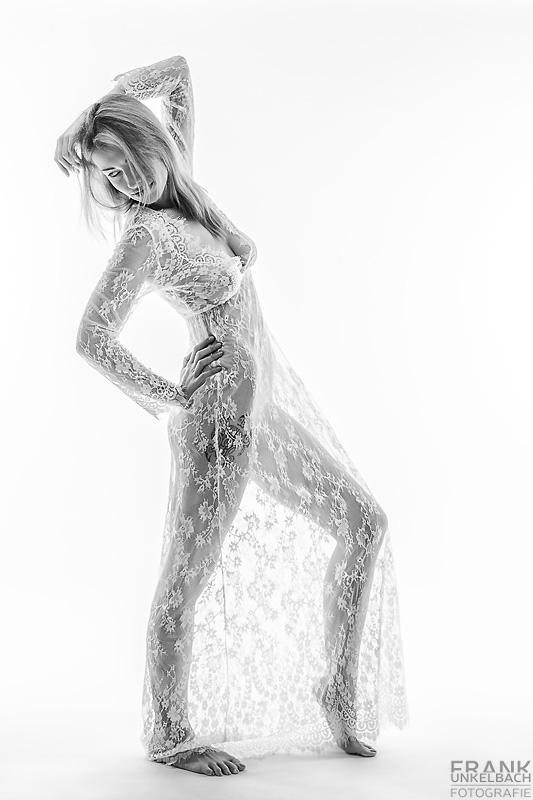 Schlanke große Frau steht nackt in sexy Netzkleid im Studio. Die Dynamik entsteht durch ihr spannendes unter interessantes Posing.