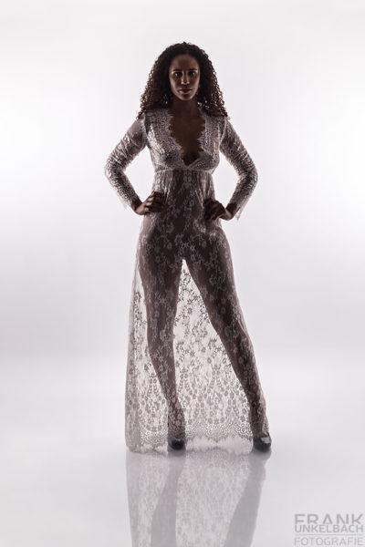 Junge Frau steht in sexy Pose und High Heels vor einer weißen Wand. Der Boden spiegelt das Netzkleid, das sie trägt.