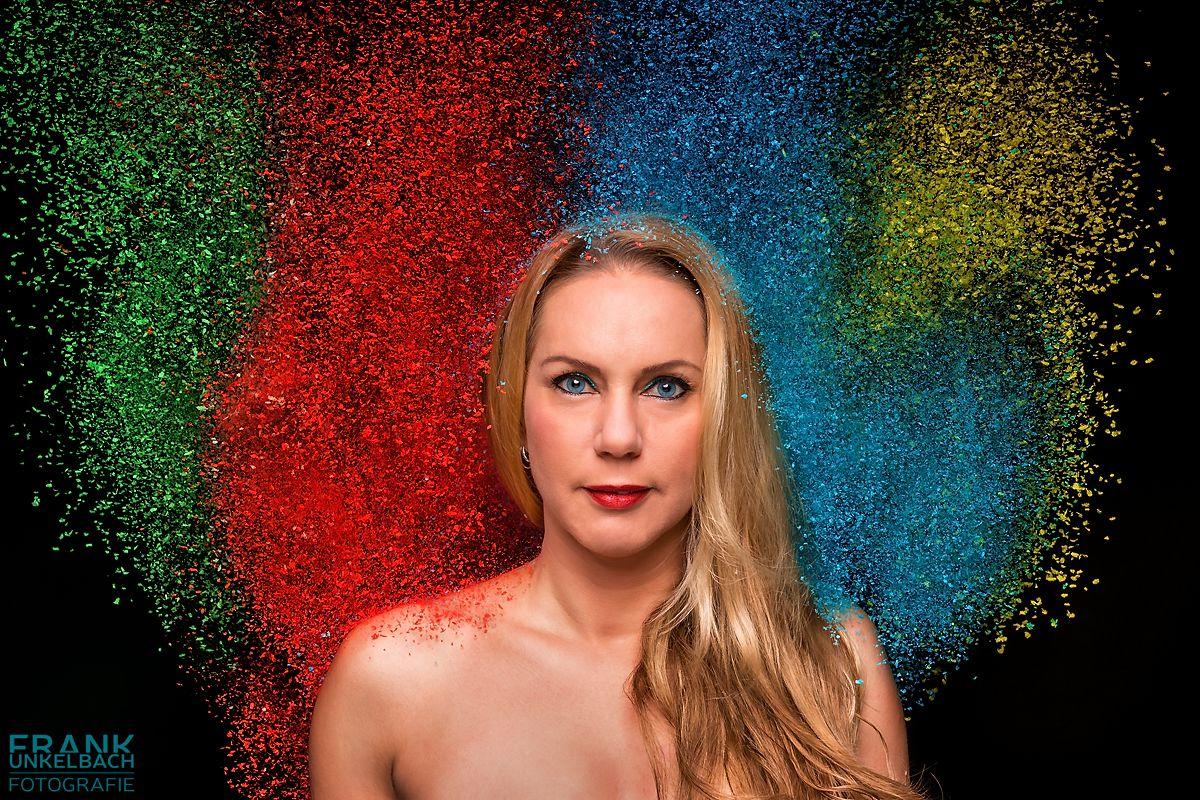 Portrait einer blonden Frau mit langen Haaren und blauen Augen. Holi-Pulver in verschiedenen Farben regnet über sie herab.