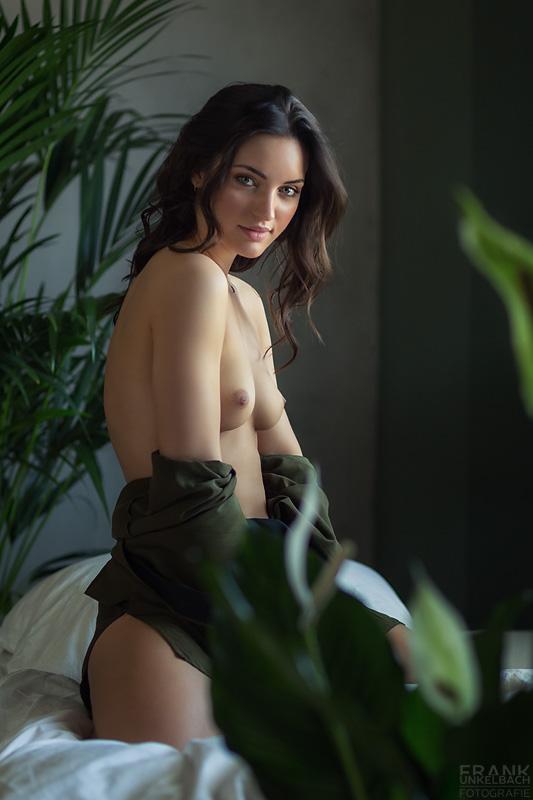 Junge Frau mit hübschen Augen, perfekten Brüsten und durchdringendem Blick sitzt fast nackt auf dem Bett.