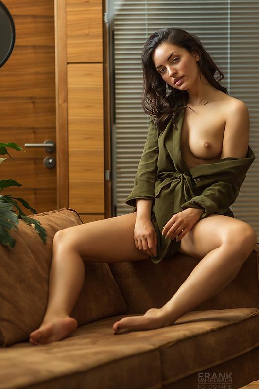 Frau braunen langen Haaren sitzt auf der Armlehne eines Sofas. Der Bademantel ist über Ihre Schulter gerutscht und entblößt Ihre Brüste.